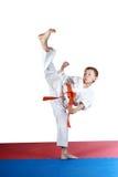 Il ragazzo nel karatege sta facendo l'alta gamba di scossa Immagine Stock