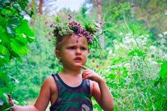 Il ragazzo nel sopporto per anima dei fiori dopo pioggia Fotografie Stock Libere da Diritti