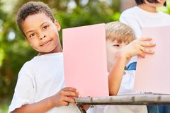 Il ragazzo nell'asilo armeggia con il cartone immagine stock