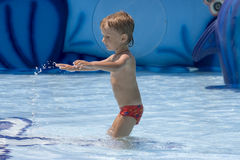 Il ragazzo nella fusione rossa gioca con acqua Fotografie Stock Libere da Diritti