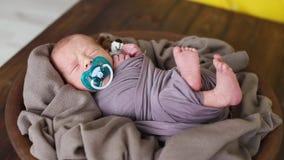 Il ragazzo neonato dorme in un piatto con un panno marrone e muove il suo piede archivi video