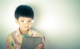 Il ragazzo nerd del genio sta utilizzando la compressa immagine stock