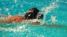 Il ragazzo nuota nello stile del movimento strisciante nello stagno stock footage