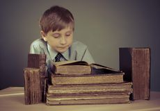 Il ragazzo passa il tempo che legge i vecchi libri Immagine Stock