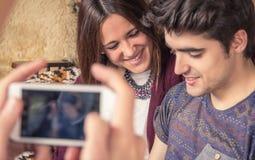 Il ragazzo passa la presa delle foto alle coppie adolescenti sul sofà Immagine Stock