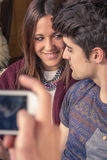 Il ragazzo passa la presa delle foto alle coppie adolescenti sul sofà Immagine Stock Libera da Diritti