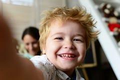 Il ragazzo passa il tempo di divertimento in stanza dei giochi Bambino con il fronte allegro fotografia stock