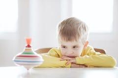 Il ragazzo premuroso si siede alla tavola ed agli sguardi alla trottola immagine stock libera da diritti