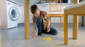 Il ragazzo pulisce i fiocchi di mais fuori dal pavimento della cucina dalle sue mani stock footage