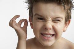 Il ragazzo pulisce il suo orecchio Immagine Stock