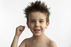 Il ragazzo pulisce il suo orecchio Immagini Stock Libere da Diritti