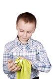 Il ragazzo pulisce il vetro con un tovagliolo. immagine stock