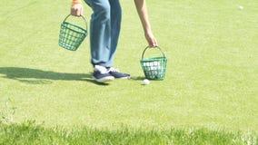 Il ragazzo raccoglie le palle da golf stock footage