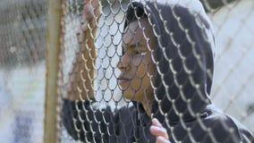 Il ragazzo razza mista sta vicino alla griglia del metallo, ritiene la barriera fra se stesso e la società stock footage