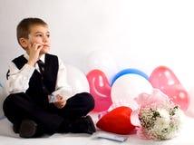 Il ragazzo riflette su una congratulazione al giorno del biglietto di S. Valentino Immagini Stock