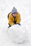 Il ragazzo rotola la neve quale Immagini Stock Libere da Diritti