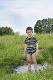 Il ragazzo rurale sporco sta a piedi nudi in una pozza Fotografia Stock