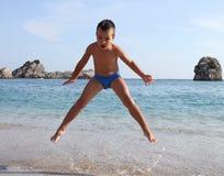 Il ragazzo salta sulla spiaggia fotografia stock