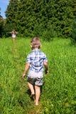 Il ragazzo scalzo va generare sulla pista fra alta erba Immagini Stock