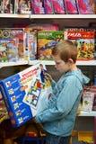 Il ragazzo sceglie un giocattolo nel deposito di giocattolo Fotografia Stock