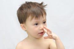 Il ragazzo seleziona il suo naso Immagine Stock