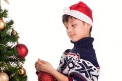 Il ragazzo si agghinda l'albero di Natale Fotografia Stock
