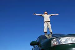 Il ragazzo si leva in piedi sulla testa dell'automobile ampiamente che dispone le mani Fotografia Stock
