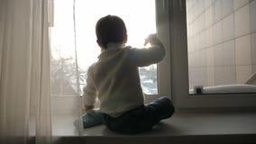 Il ragazzo si siede ad una grande finestra nell'inverno e nell'ondeggiamento stock footage