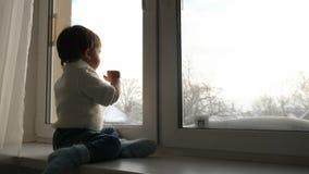 Il ragazzo si siede ad una grande finestra nell'inverno e nell'ondeggiamento video d archivio