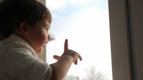 Il ragazzo si siede ad una grande finestra nell'inverno e nell'ondeggiamento archivi video