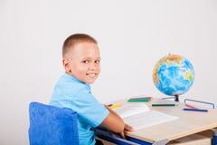 Il ragazzo si siede al suo scrittorio e compito fare immagine stock