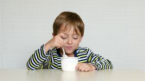 Il ragazzo si siede alla tavola e mangia il yogurt da un barattolo, avvertente le emozioni: felicità, gioia, piacere Alimento per video d archivio