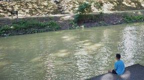 Il ragazzo si siede nella riva del fiume fotografia stock