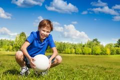 Il ragazzo si siede in squadre con la palla di pallavolo Immagini Stock