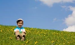 Il ragazzo si siede su un'erba Immagine Stock Libera da Diritti
