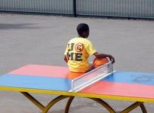 Il ragazzo si siede su una tavola di ping-pong immagine stock