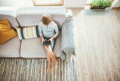 Il ragazzo si siede sui giochi del sofà con il principale vi della macchina fotografica del gamepad e dello smartphone fotografia stock libera da diritti