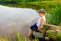 Il ragazzo si siede sulla banca del fiume. Fotografie Stock Libere da Diritti