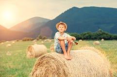 Il ragazzo si siede sulla cima del mucchio di fieno Fotografie Stock Libere da Diritti