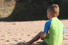 Il ragazzo si siede sulla spiaggia Fotografia Stock