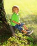 Il ragazzo si siede vicino all'albero Immagine Stock