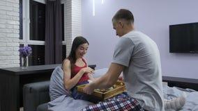 Il ragazzo sorprende la sua ragazza con la prima colazione a letto stock footage