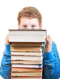 Il ragazzo sorpreso guarda fuori da dietro un mucchio dei libri Immagine Stock Libera da Diritti