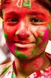 Il ragazzo sorride alla macchina fotografica coperta in pittura durante il festival di Holi dentro dentro fotografie stock libere da diritti