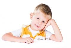 Il ragazzo sorridente attraente che si siede alla tabella ha isolato Immagine Stock