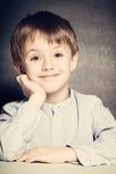 Il ragazzo sorridente del bambino si siede allo scrittorio della scuola Immagini Stock
