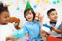 Il ragazzo sorridente prova ad indovinare che in contenitore di regalo che si siede accanto ai piccoli ospiti fotografia stock libera da diritti