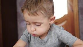 Il ragazzo sorridente sveglio estrae le matite di colore su Libro Bianco che si siede alla tavola Sviluppo e istruzione dei bambi archivi video