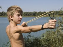 Il ragazzo spara uno slingshot Fotografie Stock