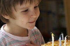 Il ragazzo spegne le candele celebratorie fotografia stock